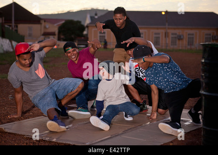 Group of adult males and boy breakdancing in park at dusk - Stock Photo