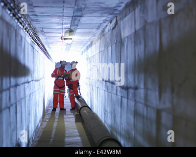 Civil engineers in discussion in tunnel of suspension bridge. The Humber Bridge, UK, built in 1981 - Stock Photo