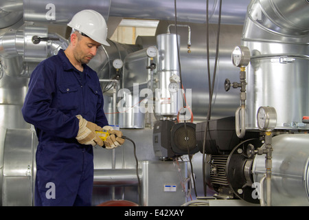 Technician monitoring pipe wiring in power station - Stock Photo