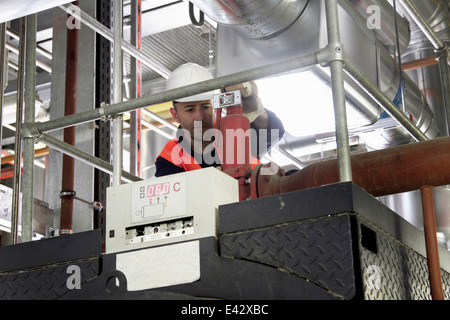 Technician on walkway doing check in power station - Stock Photo