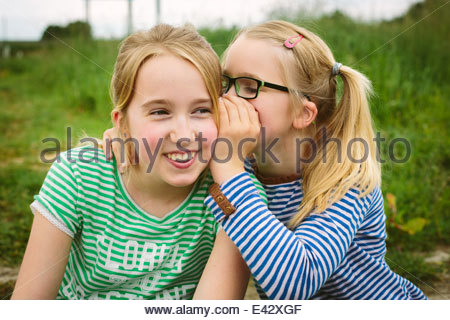 Nine year old girl whispering to sister in field - Stock Photo