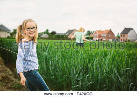Portrait of sisters in field, one running and one posing - Stock Photo