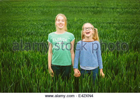 Portrait of nine year old girl and sister holding hands in field - Stock Photo