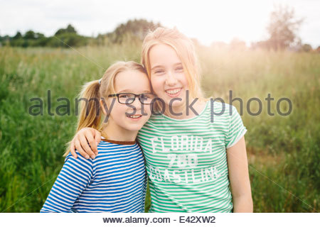 Portrait of eleven year old girl hugging sister in field - Stock Photo