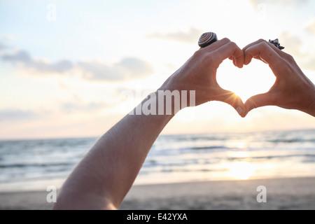 Female hands making heart shape at sunset on beach - Stock Photo