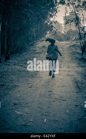 Young woman running from danger up dirt track toward apartment blocks - Stock Photo