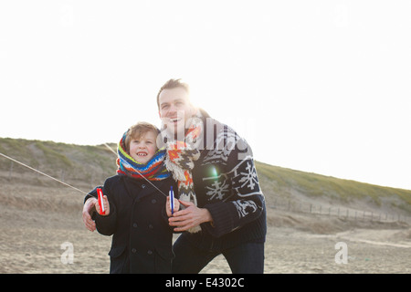 Mid adult man flying kite with son on beach, Bloemendaal aan Zee, Netherlands - Stock Photo