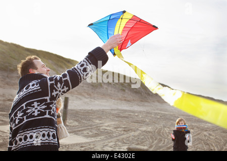 Mid adult man and son preparing to fly kite on beach, Bloemendaal aan Zee, Netherlands - Stock Photo