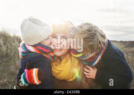 Mid adult woman with son and daughter kissing her cheek at coast - Stock Photo