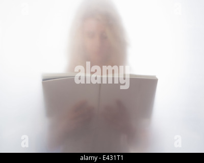 Young woman reading book behind frosted glass - Stock Photo