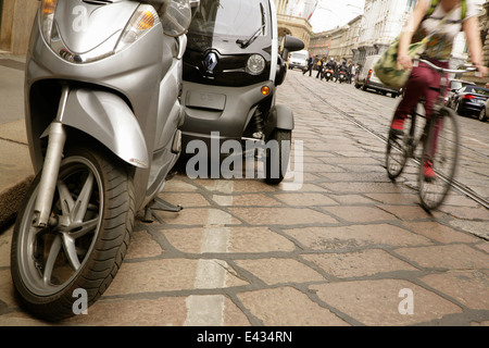Cyclist passing Renault Twizy electric microcar near La Scala, Milan, Italy. - Stock Photo