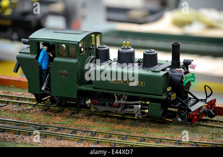 Model train green steam railway engine with driver in cab - Stock Photo