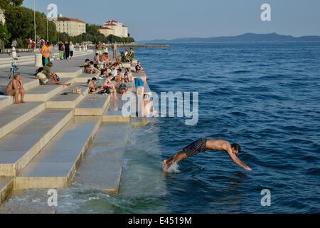 Visitors basking in the evening sun at the Sea Organ by architect Nikola Bašić, Zadar, Dalmatia, Croatia - Stock Photo