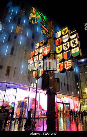 Swiss cantonal coats of arms on Leicester Square, at night, London, England, United Kingdom - Stock Photo