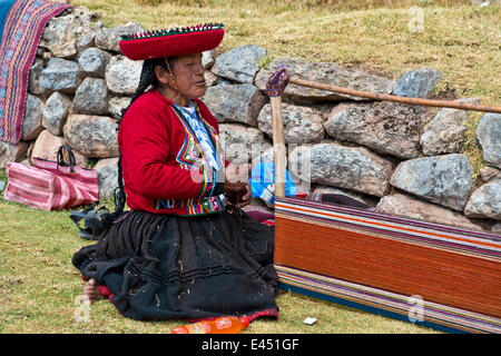 Elderly woman wearing a hat, Quechua Indian in a traditional dress, sitting on the floor and working on a stretcher - Stock Photo