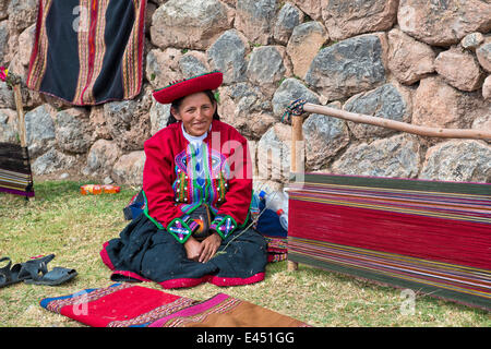Elderly woman wearing a hat, Quechua Indian in traditional dress, sitting on the floor in front of the stretcher - Stock Photo
