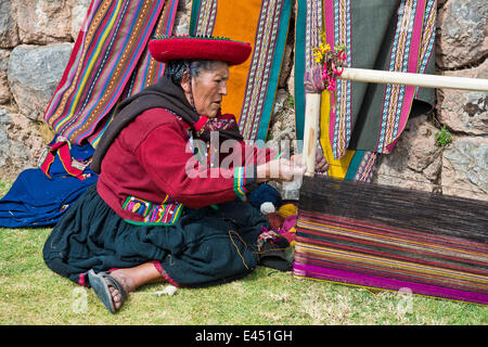 Elderly woman wearing a hat, Quechua Indian in traditional dress, sitting on the floor working on the stretcher - Stock Photo