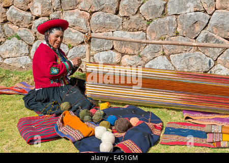 Elderly woman wearing a hat, Quechua Indian in traditional dress sitting on the floor working on the stretcher of - Stock Photo
