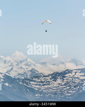 Paraglider against a blue sky, snow-capped peaks of the Alps at the back - Stock Photo