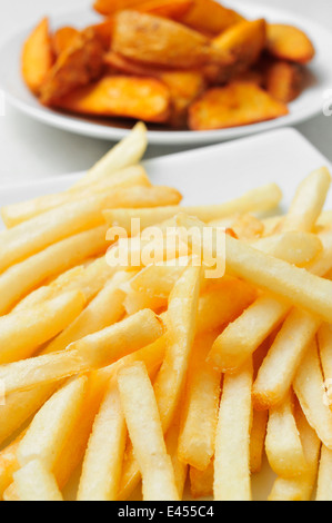 closeup of a plate with french fries and a plate with home fries in the background - Stock Photo
