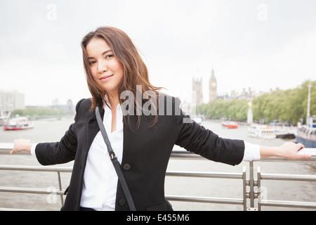 Portrait of young female tourist on Golden Jubilee footbridge, London, UK - Stock Photo
