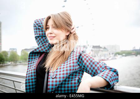 Young female tourist leaning against railings on Golden Jubilee footbridge, London, UK - Stock Photo