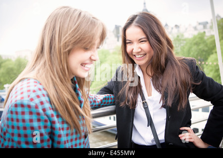 Two young female tourists giggling on Golden Jubilee footbridge, London, UK - Stock Photo