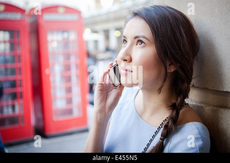Young woman on smartphone, in front of red London telephone box - Stock Photo