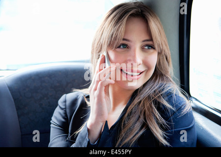 Young woman in back of taxi, on phonecall - Stock Photo