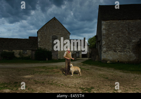 Portrait of mature traditional farmer and his lurcher dog in farmyard - Stock Photo