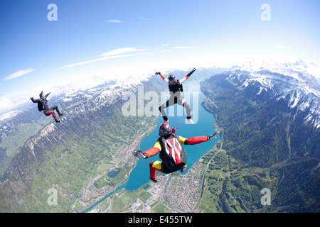 Team of three skydivers in formation over Interlaken, Berne, Switzerland - Stock Photo