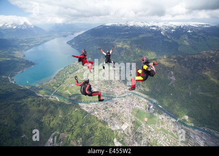 Team of four skydivers in formation over Interlaken, Berne, Switzerland - Stock Photo