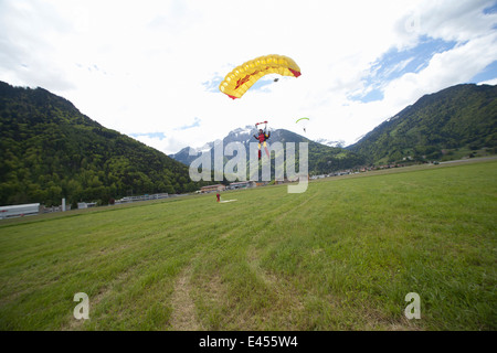 Team of three skydivers with parachutes landing in field, Interlaken, Berne, Switzerland - Stock Photo