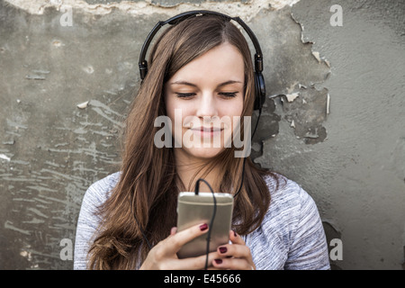 Teenage girl listening to music on smartphone - Stock Photo