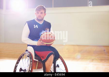 Wheelchair basketball player holding ball - Stock Photo