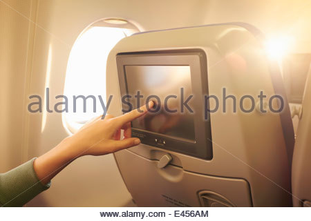 Close up of female hand using touchscreen in airplane headrest - Stock Photo
