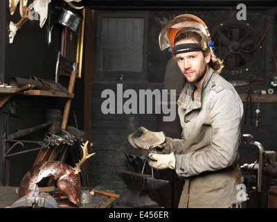 Portrait of blacksmith with a copper nail in workshop - Stock Photo