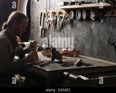 Blacksmith working with copper rivets in workshop - Stock Photo