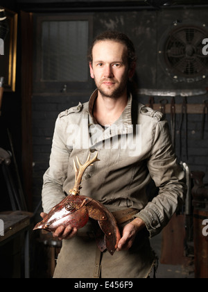 Portrait of blacksmith with a copper deer sculpture - Stock Photo
