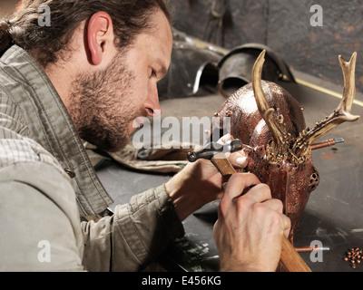 Blacksmith hammering copper on deer sculpture in workshop - Stock Photo