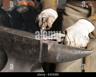 Cropped image of blacksmiths hands hammering red hot metal - Stock Photo