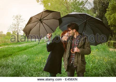 Couple walking in park under umbrellas - Stock Photo