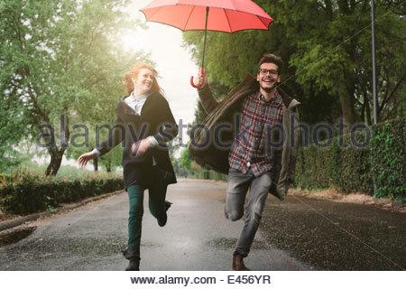 Couple running in park under umbrella - Stock Photo
