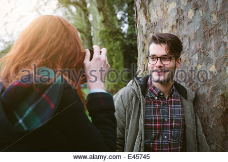 Woman photographing man leaning on tree - Stock Photo