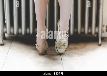 Dancer wearing one ballet shoe and one sneaker - Stock Photo