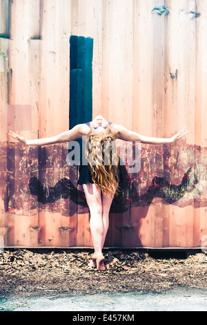 Modern dancer striking a pose in front of an abandoned shipping container - Stock Photo