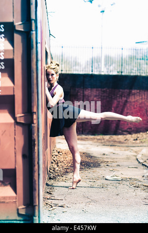 Modern dancer striking a pose in a urban park - Stock Photo