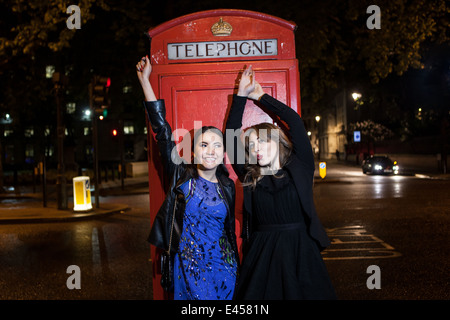 Two young female friends dancing in front of red phone box at night, London, UK - Stock Photo