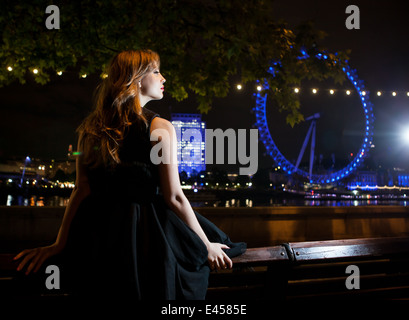 Young woman gazing at London Eye at night, London, UK - Stock Photo