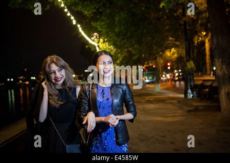 Two female friends strolling along riverside at night